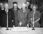 David Levine cutting a cake surrounded by woman and five men, unidentified event, April 1962