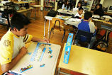 Students in Elena Velasquez's classroom where a boy in the foreground is working on a puzzle,...