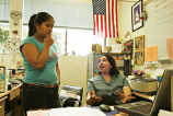 Elena Velasquez seated talking to Lizbeth, a student, in Elena's classroom, 2005