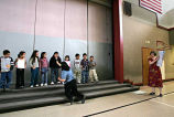 Elena Velasquez holding a microphone for children at the Bilingual Awards assembly, Forks...