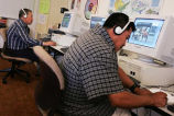 English as a Second Language students, including Don Jose, wearing headphones while working on...
