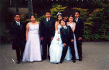 Quinceañera of Lizbeth shown in her gown posing outside St. Anne's Church with some chambelanes...