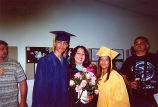 Elena Velasquez with Javier and Aris in graduation cap and gown with two men standing nearby,...