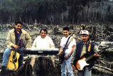 Los Leñadores de Forks band members standing in clearcut with musical instruments, possibly in...