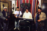 Los Leñadores de Forks band members standing inside a room with musical instruments, possibly in...