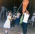 Cecilia at her birthday party hitting a piñata with other children nearby, Mexico, ca. 1985