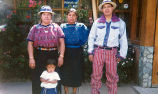 Adults (two women and a man) with a child outside a house in Todos Santos Cuchumatán, Guatemala,...