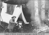 Man preparing a meal near tent and laundry at Longmire Springs, Mount Rainier, ca. 1894