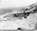Mining operation showing miners working, eating within view of cabins and flumes, Hunker Creek,...