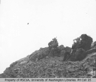 Men with camping and climbing equipment on rocky hillside, July 23, 1910