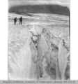Two men peering into crevasse on Stevens Glacier, southeast slope of Mount Rainier, ca. 1901