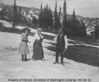 Two women and a man standing in snowfield, vicinity of Mount Rainier, 1909