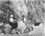 Hikers including two women, one of them Mrs. H. M. Sarvant,  resting by boulders, Mount Rainier,...