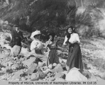 Three women, one of them Mrs. H. M. Sarvant,  and man picnicing near the foot of a glacier, Mount...
