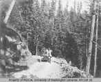 Women on automobile excursion on gravel road in woods, vicinity of Mount Rainier, August 16, 1908