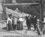 Group of people and two automobiles on wooden bridge with Mrs. H. M. Sarvant on left, vicinity of...