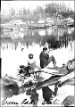 Two boys with fishing pole and gun sitting on log debris in Green Lake, 1895