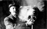 Proprietor, Curio Joe, of the Ye Olde Curiosity Shop holding a stuffed bears head, n.d.