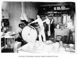 H.J. Kingsbury and two men operating machinery inside the North Seattle Printing Co. shop at 1112...