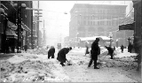 Shoveling snow at 1st Ave. and Yesler Way after a storm, winter 1916