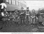 Group of Lapland (Sami) herders standing near a passenger train, Lapland-Yukon Relief Expedition,...