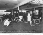 Unidentified men working on tires and axles of Ford automobiles, William O. McKay Company,...