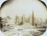 Aftermath of the Seattle Fire of June 6, 1889 showing a group of people standing in the ruins of...