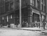 Group of men with shovels and crates outside the Schwabacher Brothers and Company offices,...