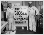 Painters Clarence Sewell, at left, and Don Nagle in front of one of their signs at the Century 21...