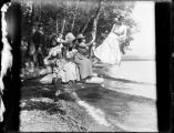 Group of women and children sitting on large tree branch on shore of Lake Washington, 1900