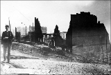 Aftermath of the Seattle fire of June 6, 1889 showing Washington National Guard member standing to...
