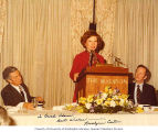 Representative Brock Adams listening to speech being made by Rosalynn Carter, ca. 1976