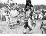 Man wearing thunderbird spirit dance costume and a woman holding stick with paddles at a...
