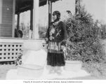 Lummi Native American woman wearing traditional dress standing with checker woven baskets,...