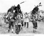 Men in spirit dance costumes playing drums and walking at traditional Lummi Native American dance,...