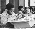 African-American boy painting at desk in a classroom, Washington, n.d.