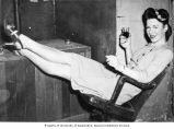 Wanda Brown reclining in a chair, holding a drink and a cigarette, n.d.
