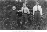 Three boys standing near a bicycle, October 13, 1922