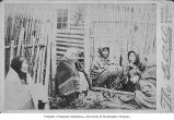 Group of Native American women seated along side log house, possibly British Columbia, ca....