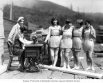 "Four ""Spruce Girls"" wearing spruce veneer bathing suits and two girls at a sewing..."