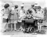 "Five ""Spruce Girls"" holding spruce veneer bathing suits while a sixth girl sits at a..."