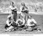 Five sheep shearing girls wearing overalls on a lawn holding lambs, possibly Washington State, ca....