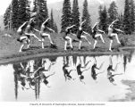 Ivan Novikoff dancers in swimsuits posing by and reflected in a lake, Washington State, ca....