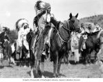 Native American man riding a hooded horse with other Native Americans on horseback at the...