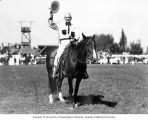 Harry Anderson, the founding father of the Ellensburg Rodeo, sitting on horseback and waving his...