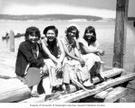 Four Native American girls sitting on a dock to watch the canoe race at the Coupeville Native...