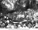 Crowd surrounding a woman skating around a giant skillet with slabs of bacon tied to her feet,...