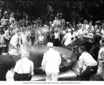 Seven men, two dressed as chefs, adjust the position of a giant skillet in an attempt to create...