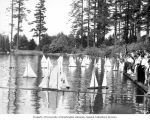 Crowd of children standing on the dock watching toy sailboats at Laurelhurst Park, Seattle,...