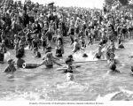 Crowds of people in the water and on the shore at Greenlake beach, Seattle, Washington, ca....